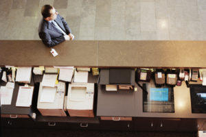 Businessman waiting at front desk in hotel, elevated view